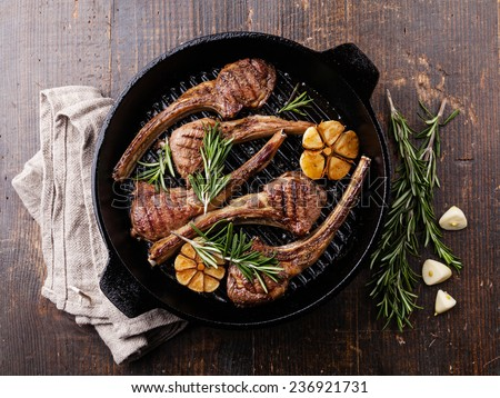 Roasted lamb ribs with rosemary and garlic on grill pan on dark background - stock photo