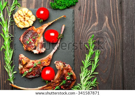 Roasted lamb ribs with spices, tomatoes and garlic on black stone background