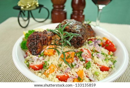 Roasted lamb shank and rosemary on tomato, butternut pumpkin and parsley couscous. - stock photo
