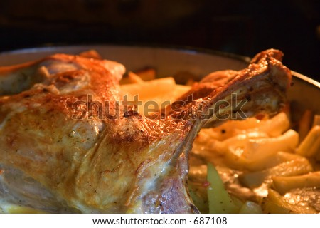 Roasted lamb with baked potatoes cooking inside the oven - stock photo