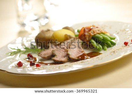 roasted lamb with beans in bacon and potatoes - stock photo