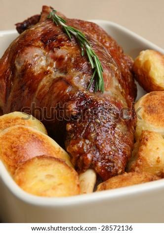 roasted leg of lamb with roast potatoes. - stock photo