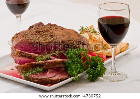 Roasted leg of lamb with roasted potatoes and glass of wine - stock photo