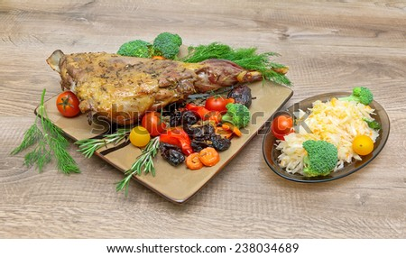 roasted leg of lamb with vegetables and herbs on a wooden background. horizontal photo. - stock photo