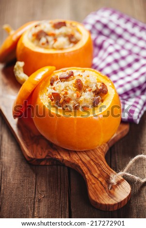 Roasted little pumpkins stuffed with chicken meat, vegetables and rice - stock photo