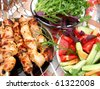 roasted meat on the spits with vegetables and greens - stock photo
