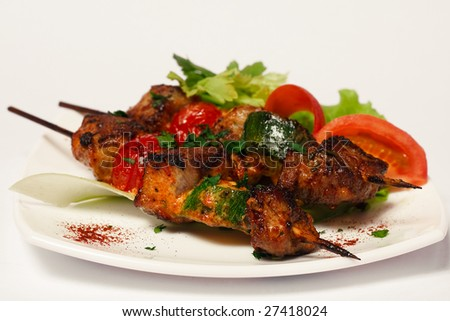 roasted meat on wood sticks with fresh vegetables on a white plate - stock photo