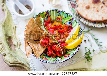 Roasted mediterranean vegetables with flat bread and herbs (rosemary, marjoram). Top view, selective focus. - stock photo