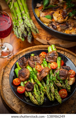 Roasted mushrooms with green asparagus and red wine - stock photo