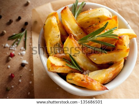 Roasted or baked potatoes with rosemary in a white bowl on wooden background - closeup rustic composition from above - stock photo