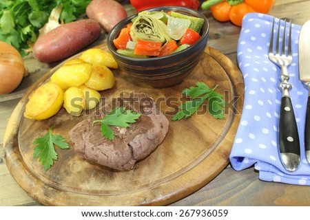 roasted ostrich steaks with baked potatoes and parsley on a wooden board