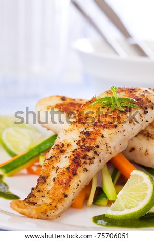 Roasted pangasius fish meal with vegetable in a white plate.
