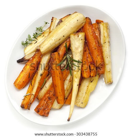 Roasted parsnips and carrots garnished with rosemary and thyme.  White plate, overhead view. - stock photo
