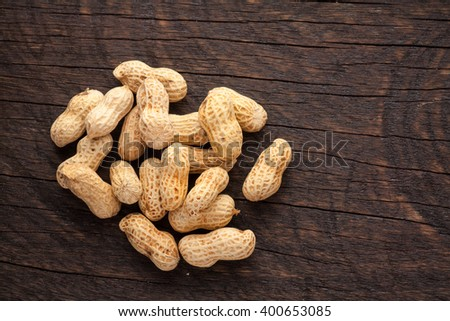 Roasted peanuts scattered on rustic, dark wood background - stock photo