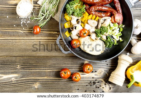 roasted pepper sausage mushrooms tomatoes green vegetables in a frying pan on a wooden table top view of the cooking process - stock photo