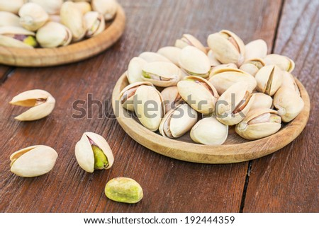 Roasted pistachio on wooden plate - stock photo