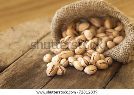 Roasted pistachios on natural wooden table background - stock photo