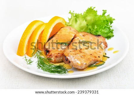 Roasted pork chop with orange sauce on white plate - stock photo