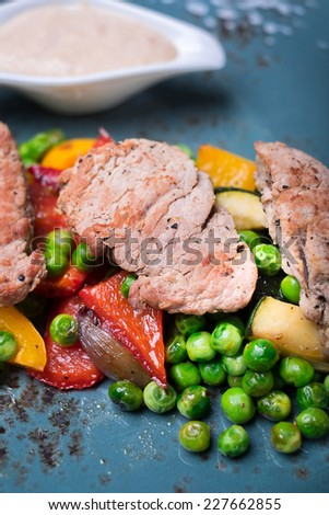 Roasted pork fillet meat with frozen peas, red belle pepper, zucchini, eggplant with cream sauce on a plate - stock photo