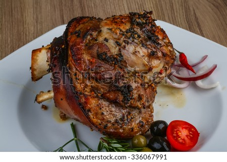 Roasted pork knee with dill and rosemary on the wood background