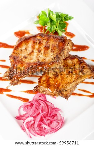 Roasted pork meat at plate with greens - stock photo