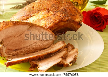 roasted pork on a white plate among spices - stock photo