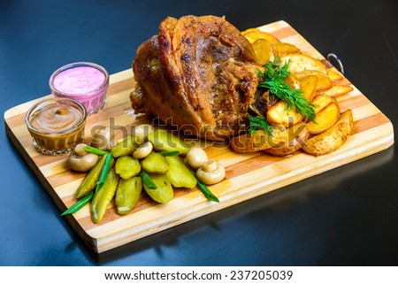 roasted pork shank with potatoes on wooden board - stock photo