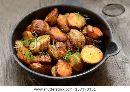 Roasted potato in a frying pan on wooden table - stock photo