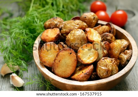 Roasted potato in bowl on wooden table - stock photo