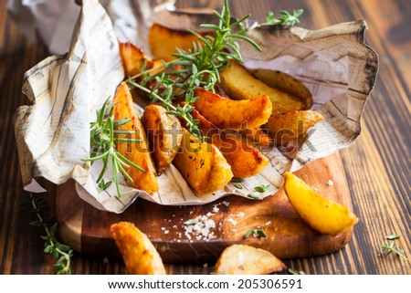 Roasted potato wedges with herbs and salt - stock photo