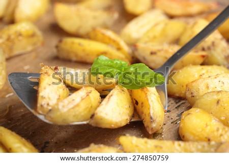 Roasted potato with basil leaf on a baking sheet. Selective focus on the basil leaf - stock photo