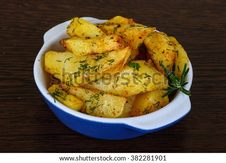 Roasted potato with dill and rosemary on the wood background