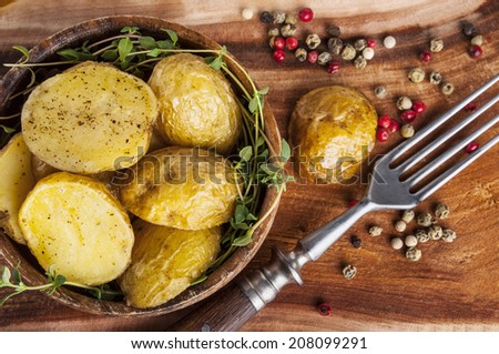 Roasted potato with spice in bowl on wooden table - stock photo