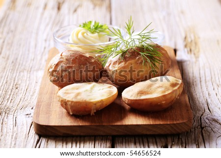 Roasted potatoes, butter and salt - stock photo