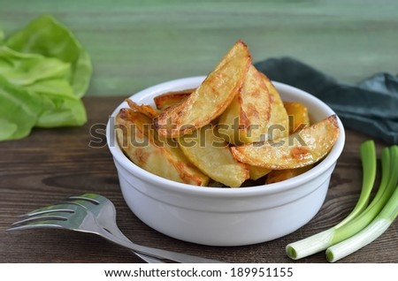 Roasted potatoes in a white bowl - stock photo