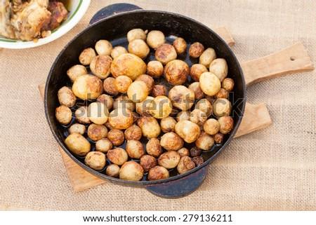 roasted potatoes in iron pan - stock photo