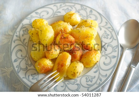 roasted potatoes on dish close up - stock photo