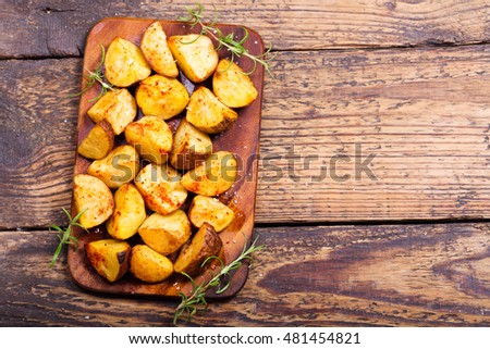 roasted potatoes with rosemary on wooden table, top view