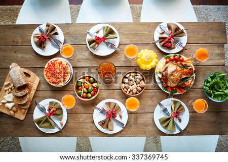 Roasted poultry, glasses with juice, vegetables, nuts and tableware on served table - stock photo