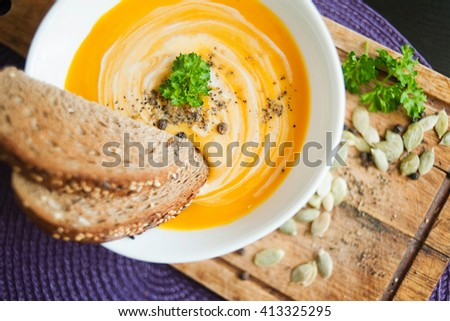 Roasted pumpkin and carrot soup with cream and pumpkin seeds on  - stock photo