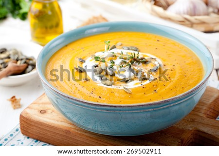 Roasted pumpkin and carrot soup with cream and pumpkin seeds on white wooden background. Copy space - stock photo