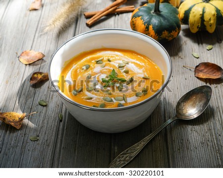 Roasted pumpkin and carrot soup with cream and pumpkin seeds on white wooden background/ Selective focus  - stock photo