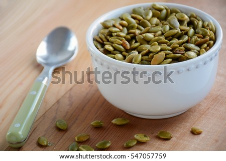 Roasted pumpkin seeds in white decorative bowl with green spoon on cedar background.  Horizontal format with shallow depth of field.