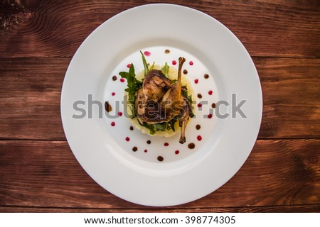 Roasted quail on a bed with mashed potatoes, rocket leaves and berry sauce. On a white plate and wooden rustic background. Top view - stock photo