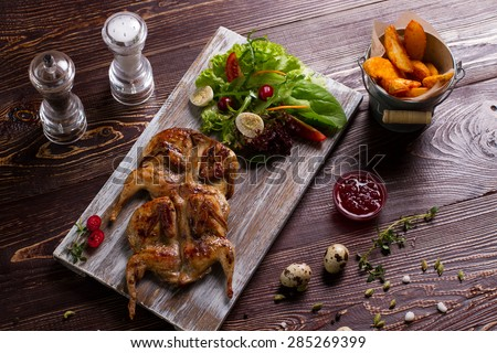 Roasted quail with salad and potatoes. Exclusive dish. Beautiful still life of food. - stock photo