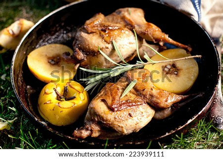 Roasted quails with quince on a cast iron skillet outdoor - stock photo