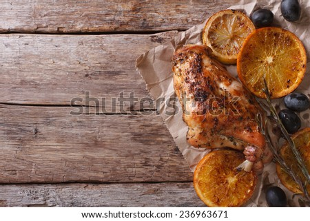 roasted rabbit leg with oranges and olives on an old table. horizontal view from above  - stock photo