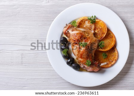 roasted rabbit leg with oranges, olives on a white plate. horizontal view from above  - stock photo