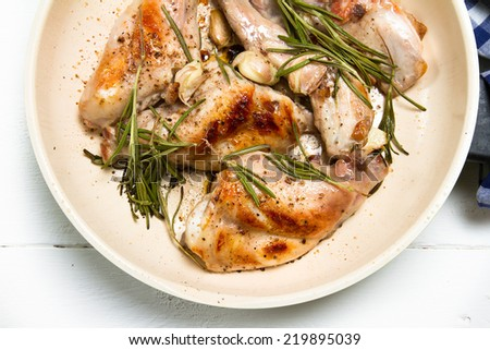 Roasted rabbit thighs with garlic and rosemary - stock photo