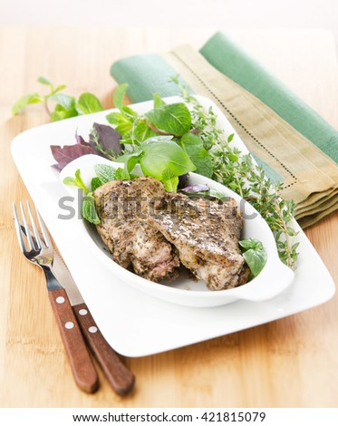 roasted rabbit with rosemary and thyme garlic in a ceramic dish on a linen napkin - stock photo